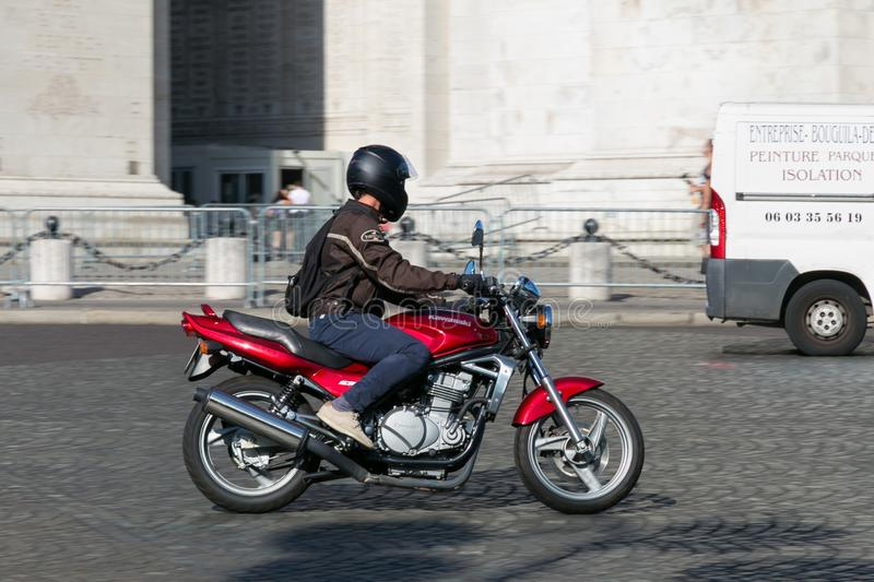 PARIS, FRANCE - JUNE 23, 2017: Unknown adult male on a motorcycle in the center of Paris at summertime. Unknown adult male on a motorcycle in the center of Paris royalty free stock photos