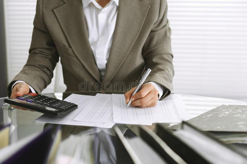 Bookkeeper woman or financial inspector making report, calculating or checking balance, close-up. Business, audit or tax. Unknown bookkeeper woman or financial royalty free stock photos