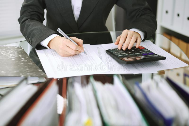 Bookkeeper woman or financial inspector making report, calculating or checking balance, close-up. Business, audit or tax. Unknown bookkeeper woman or financial stock image