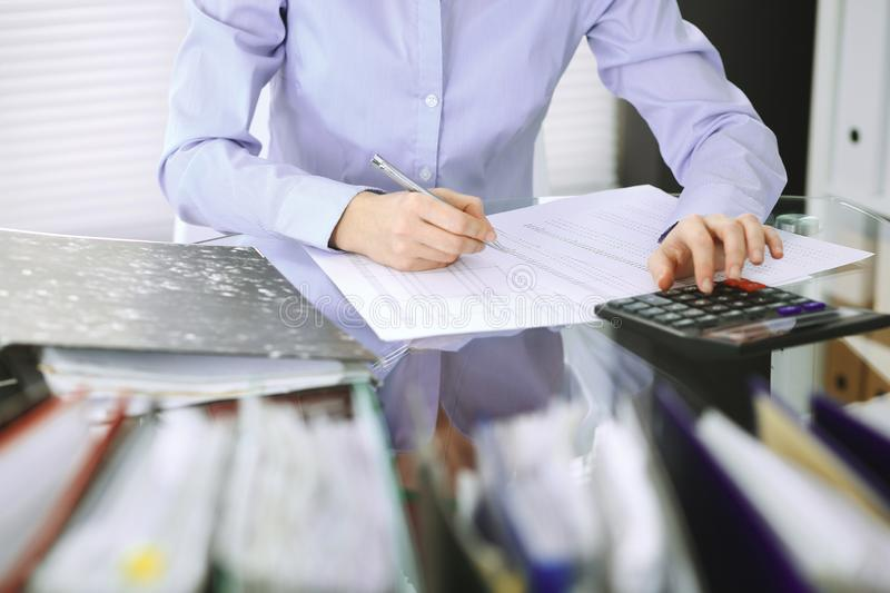 Bookkeeper woman or financial inspector making report, calculating or checking balance, close-up. Business, audit or tax. Unknown bookkeeper woman or financial royalty free stock image