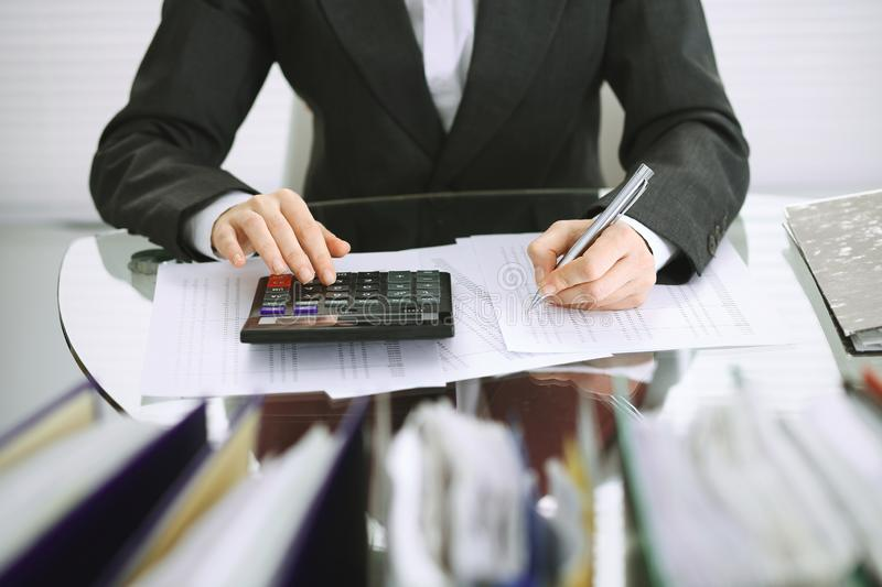 Bookkeeper woman or financial inspector making report, calculating or checking balance, close-up. Business, audit or tax. Unknown bookkeeper woman or financial royalty free stock photography