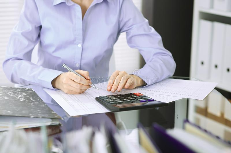 Bookkeeper woman or financial inspector making report, calculating or checking balance, close-up. Business, audit or tax. Unknown bookkeeper woman or financial royalty free stock images