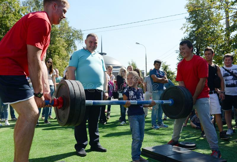 An unknown boy is trying to lift a bar at a sports festival. MOSCOW, RUSSIA - AUGUST 22, 2015:An unknown boy is trying to lift a bar at a sports festival stock image
