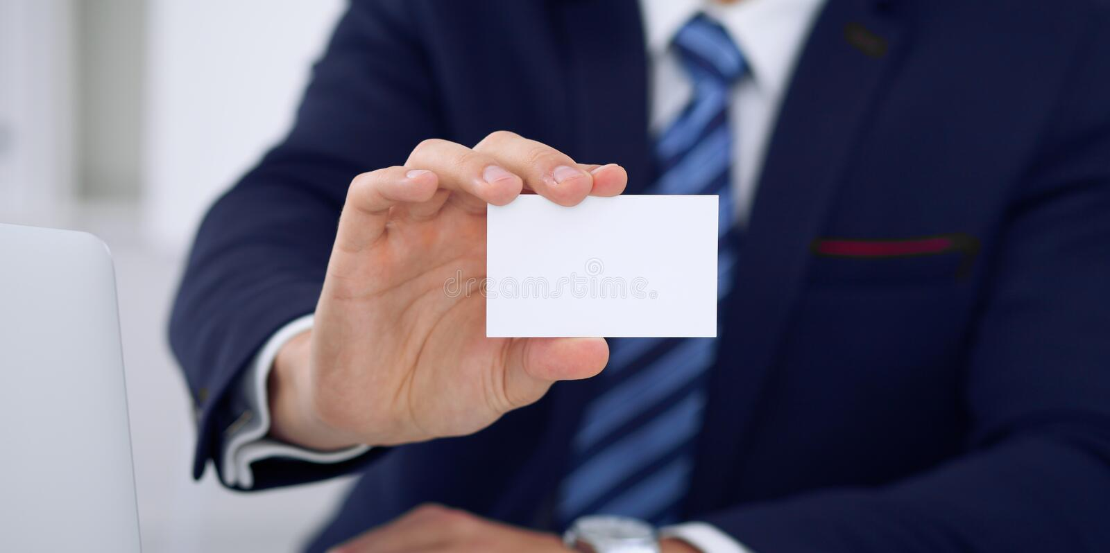 Unknown businessman or lawyer giving a business card while sitting at the table, close-up. He offering partnership an royalty free stock images