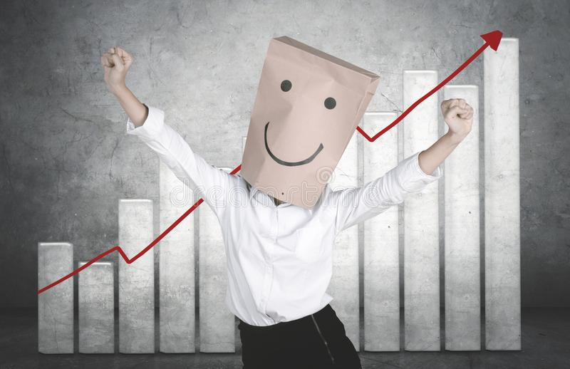Unknown businesswoman celebrating her success. Unknown businesswoman with paper bag on her head while celebrating her success with growth finance graph royalty free stock photos