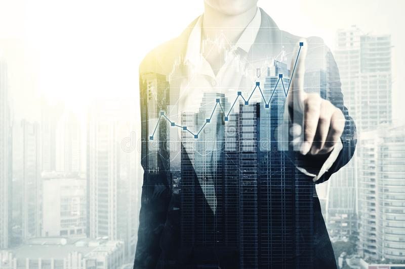 Unknown businesswoman with double exposure. Double exposure concept. Unknown businesswoman touching growth finance graph on the virtual screen, skyscraper in the royalty free stock images