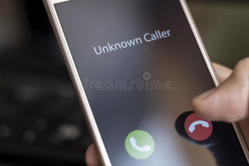 Unknown caller. A man holds a phone in his hand and thinks to end the call. Incoming from an unknown number. Incognito or royalty free stock images