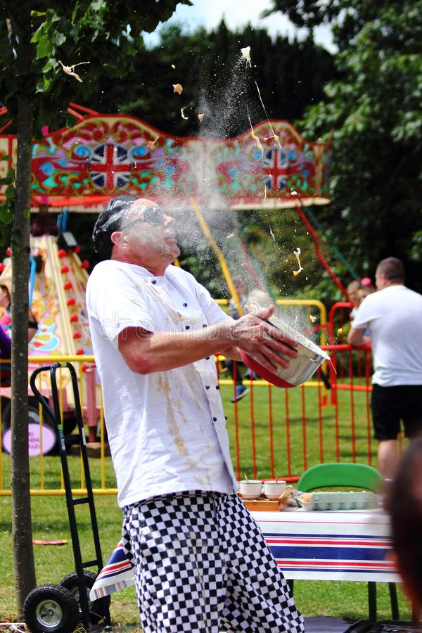 An Unknown Chef Shows Off to the Croud as he Tries to Catch an Egg in a Bowl. Crawley Festival, High Street, Crawley, West Sussex, United Kingdom, 1 July 2017 stock photos