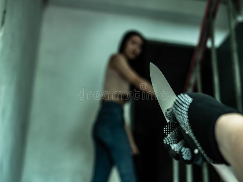 Unknown criminal guy with knife chasing young girl. Robbery or rape in gangster district concept, a person or thing that is likely royalty free stock photography