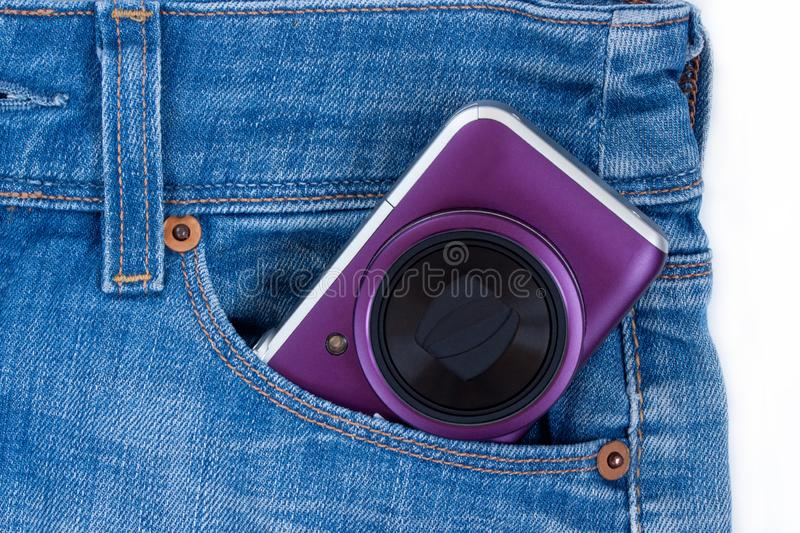 Unknown digital camera is lying in the side pocket of blue jeans. The concept of holiday and traveling royalty free stock photos