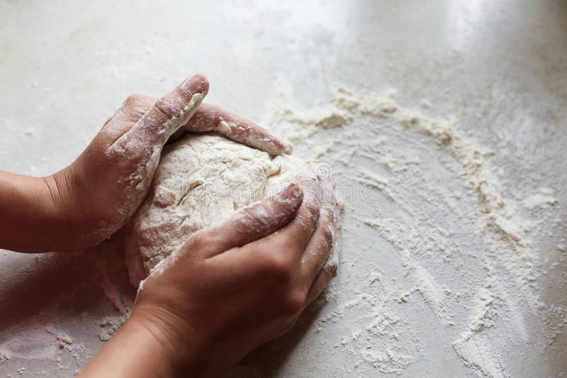 Unknown female hands making dough for pastry, having enough flour on white table, practising baking skills, spending her free time. At kitchen, making shape of stock photo