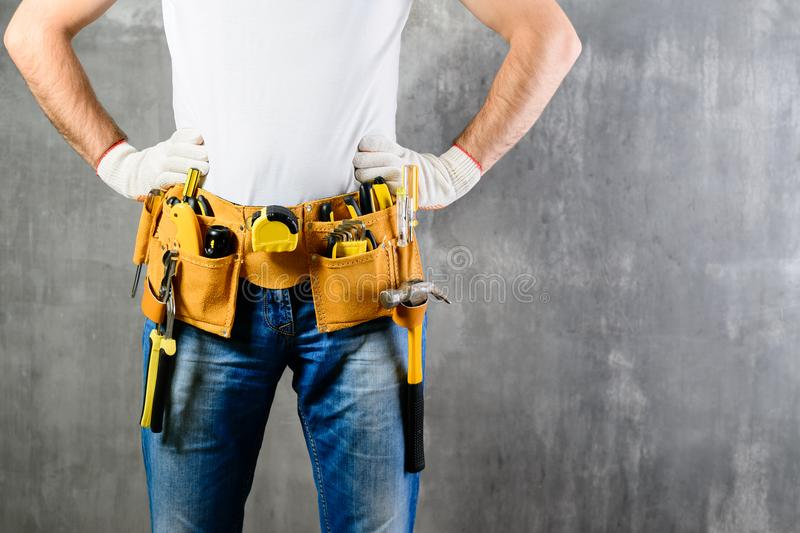 unknown handyman with hands on waist and tool belt with construction tools against grey background with copyspace for text. DIY t royalty free stock photos