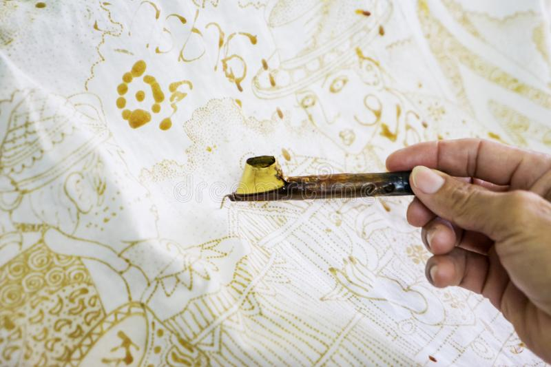 Unknown man using a canting. Hand of unknown man using a canting and wax for making batik on a fabric in Yogyakarta stock image
