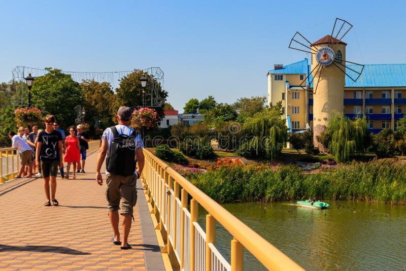 Unknown people walking on pedestrian bridge  across Khorol river in wellness resort Myrhorod royalty free stock images