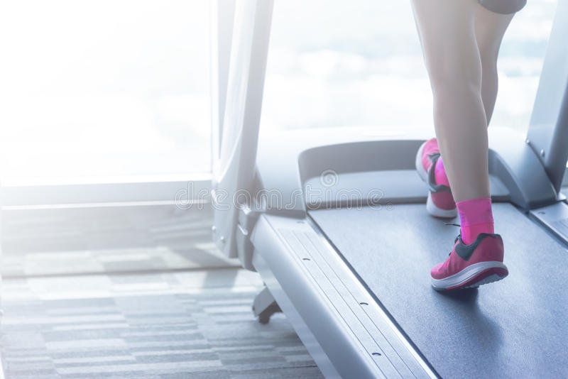 Unknown woman in pink shoes running on thread mill stock images
