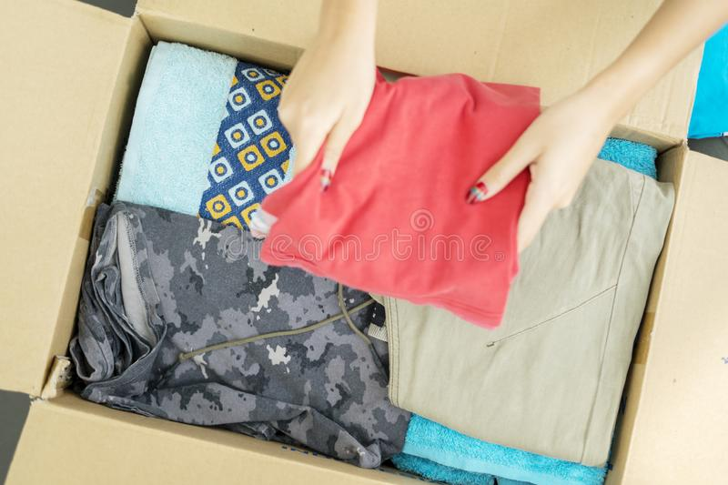 Unknown woman putting clothes in a cardboard box royalty free stock images