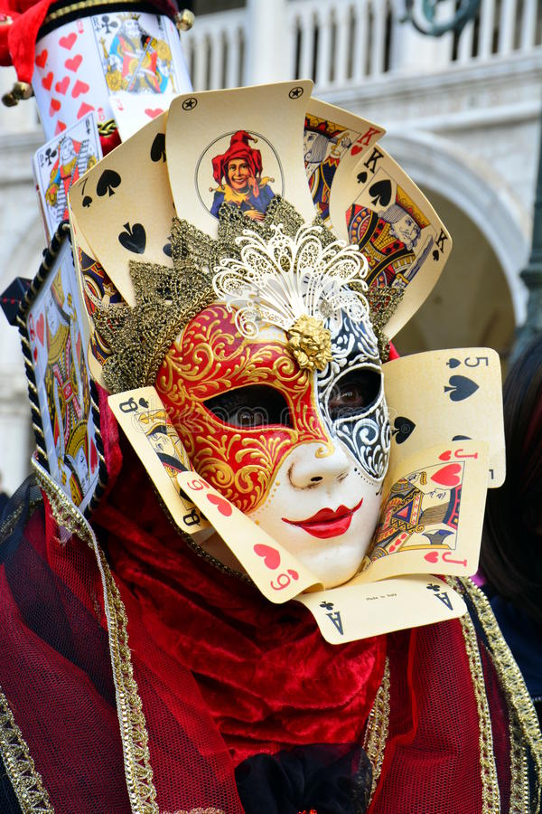 an unknown woman with two colored mask with face and court cards