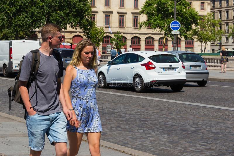 PARIS, FRANCE - JUNE 23, 2017: Unknown young couple walking near the cobblestone road in the center of Paris stock photos