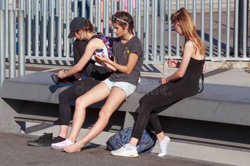 BARCELONA, SPAIN - MAY 16, 2017: Unknown young girls sitting on a bench in center of Barcelona in Port Vell at sunny day. Unknown young girls sitting on a bench royalty free stock images