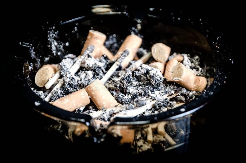 Unkosten der brennenden Zigarette im Aschenbecher lizenzfreies stockfoto