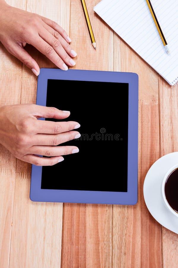 Unkosten der weiblichen Hand unter Verwendung der Tablette stockfoto