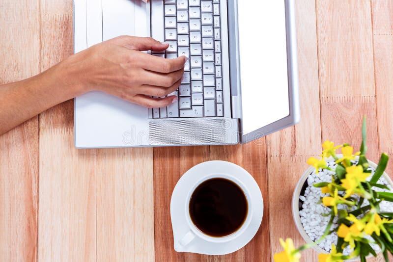 Unkosten der weiblichen Hand unter Verwendung des Laptops stockfoto