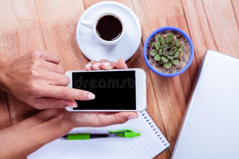 Unkosten der weiblichen Hand unter Verwendung des Smartphone lizenzfreies stockfoto