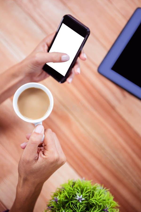 Unkosten der weiblichen Hand unter Verwendung des Smartphone lizenzfreie stockbilder
