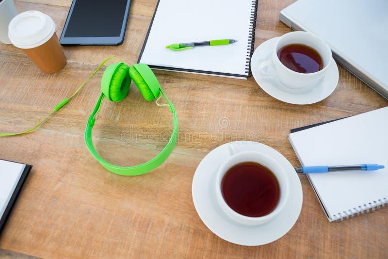Unkosten des Kaffees und des Kopfhörers auf dem Schreibtisch stockfotos