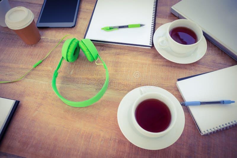 Unkosten des Kaffees und des Kopfhörers auf dem Schreibtisch lizenzfreie stockfotos
