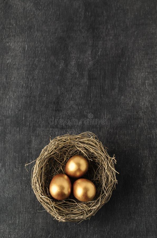 Unkosten des Nestes drei Goldeier auf Tafel Backgr enthalten lizenzfreie stockfotos