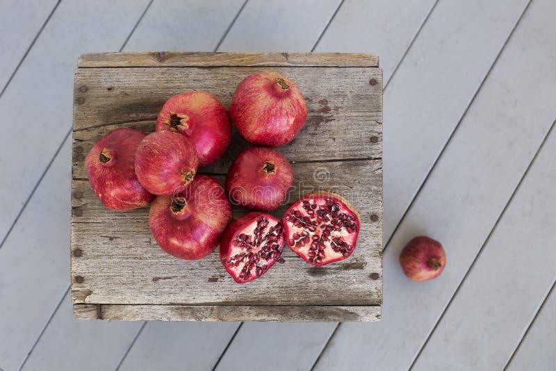 Unkosten von Granatäpfeln auf verwittertem Holz stockbild