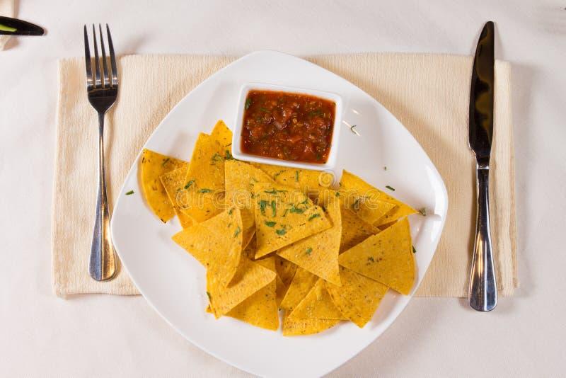 Unkosten von Nacho Chips und von Salsa auf Platte stockfotografie
