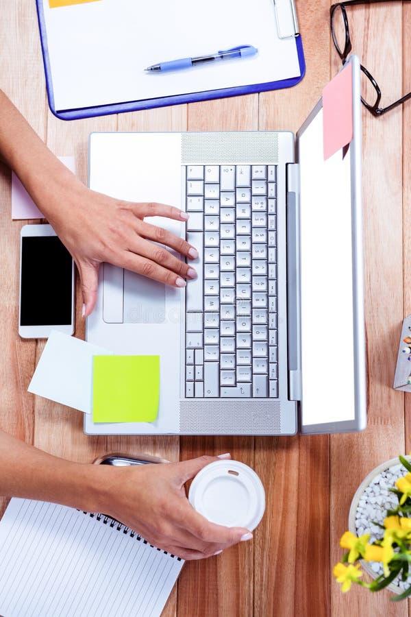 Unkosten von weiblichen Händen unter Verwendung des Laptops und des Haltens der Kaffeetasse stockbild