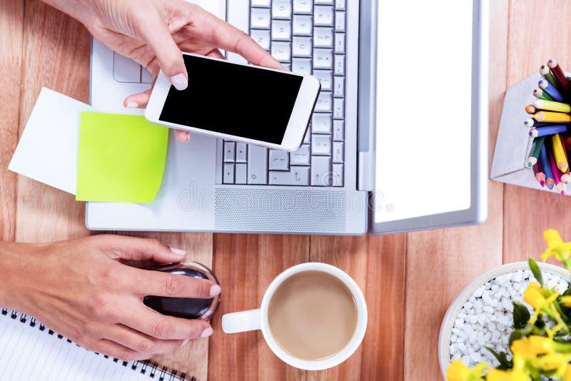 Unkosten von weiblichen Händen unter Verwendung des Smartphone und der Maus lizenzfreies stockfoto
