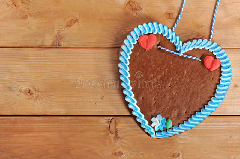 Unlabeled Bavarian gingerbread heart. Original unlabeled bavarian gingerbread heart from Germany on old weathered wooden board stock photo