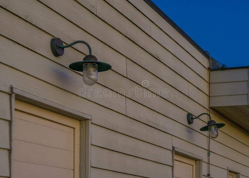 Unlit lanterns hanging on the wooden wall of a house, outdoor lighting in vintage style. A unlit lanterns hanging on the wooden wall of a house, outdoor lighting stock images
