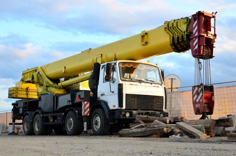 Unloading of cargo and building materials by mobile truck crane at the construction site. stock photos