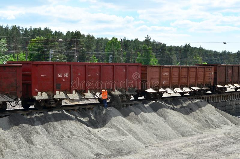 Unloading bulk cargo from railway wagons on of high railway platform. Unloading of crushed stone from railway car. Unloading bulk cargo from railway wagons on royalty free stock images