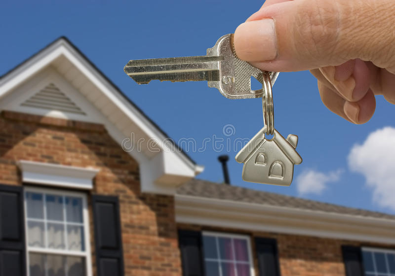 Unlocking Your Door. A key on a house keychain in a persons hand on a house and sky background, unlocking your door royalty free stock photography
