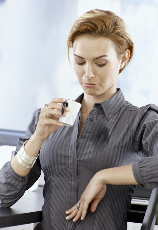 Unlucky businesswoman spilling coffee on blouse royalty free stock image