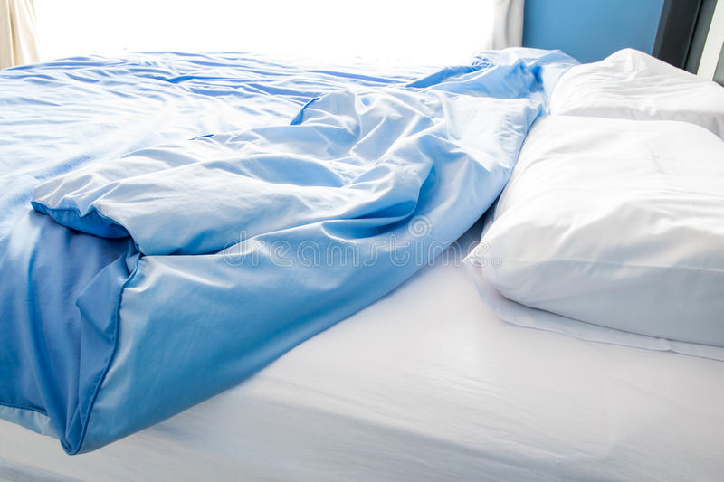 Unmade bed with white pillow royalty free stock photos