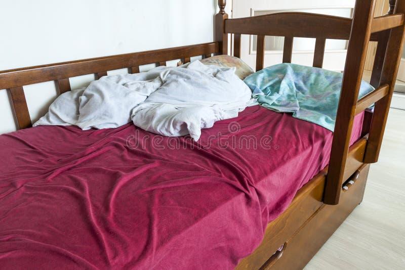 Unmade dziecka łóżko z zmiętymi łóżkowymi pościelami i pigułką czerwieni i białych zdjęcie royalty free