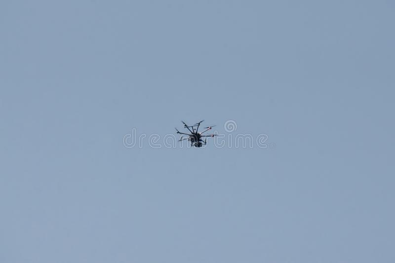 Unmanned aerial vehicle - quad copter with a camera and broadcast video flies in the blue sky royalty free stock images