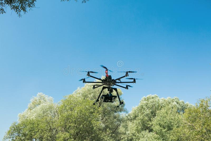 Unmanned aircraft in black, flying with a digital camera. Demon with a digital camera of high resolution. The flying royalty free stock image
