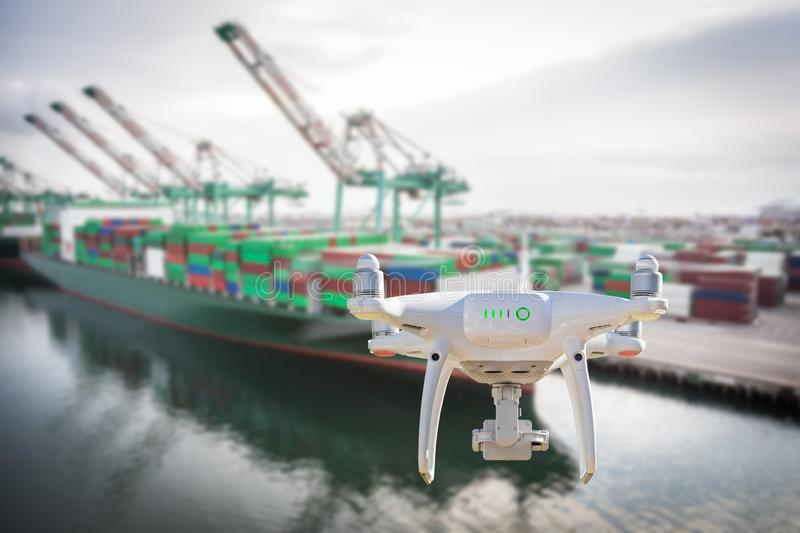 Unmanned Aircraft System Quadcopter Drone In The Air Near Large Shipping Vessel and Dock with Crates.  stock image