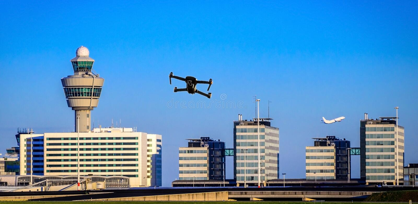 Unmanned drone flying near airport with air traffic control tower, flight disruption concept - digital composite royalty free stock photography