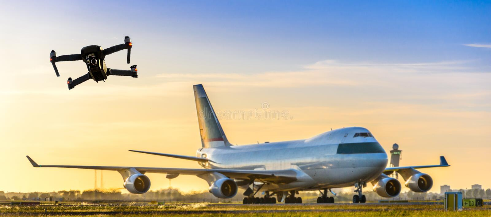 Unmanned drone flying near large commercial airplane at airport - flight disruption concept royalty free stock image