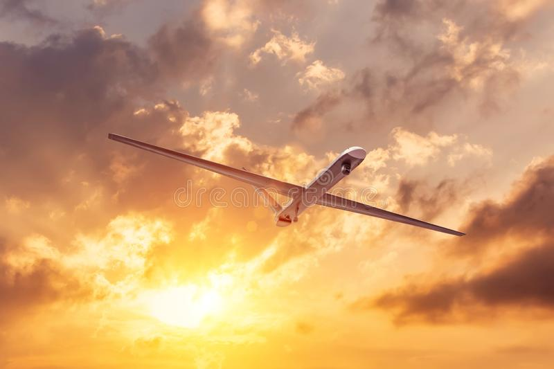 Unmanned military drone flies the at sunset clouds sky stock images