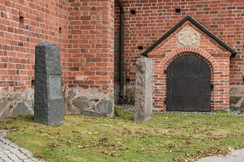 Unmarked graves outside an old brick church building. Two tall grave stones standing outside an old brick church in Sweden royalty free stock photos